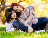 Two beautiful teen girl at green grass in the park. — Stock fotografie