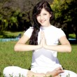 Beautiful young brunet yoga girl on green grass in park. — Stock Photo