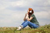 Young fashion girl with headphones at grass in spring time. — Stock Photo