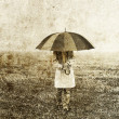 Girl with umbrella staying on field. — Stock Photo
