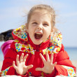 Happy little girl at the beach in spring time. — Stock Photo