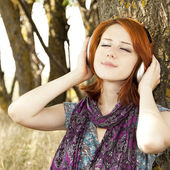 Young smiling fashion with headphones near tree. — Stock Photo