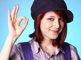 Beautiful girl in shirt and violet cap show OK — Stock Photo