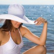 Girl in a white hat on the beach - Stock Photo