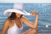 Girl in a white hat on the beach — Stock Photo