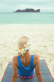 Close-up of woman seating on the beach with flowers in her hair looking to the sea — Stock Photo