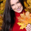 Young woman in autumn park holding yellow leaf — Stock Photo