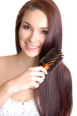 Young woman brushing her long hair — Stock Photo