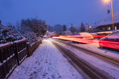 Car lights streaming by on a snowy evening — Stock Photo