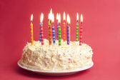 Birthday cake on red background — Stok fotoğraf