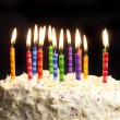 Birthday cake and candles on black background — Stock Photo #5036259
