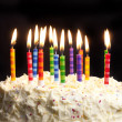 Birthday cake and candles on black background — Stock Photo