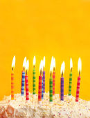 Birthday cake on yellow background — Stock Photo