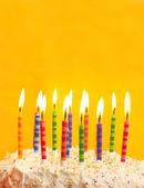Birthday cake on yellow background — Stock Photo