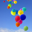Lots of coloured balloons flying into the sky — Stock Photo