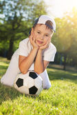 Cute little boy with a ball in beautiful park in nature; — Stock Photo