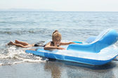 Girl on inflatable mattress in sea — Stock Photo