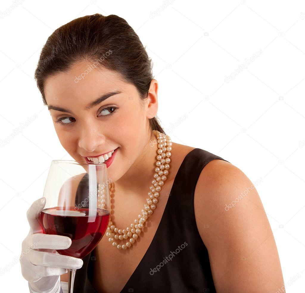 A beautiful smiling woman in a classy dress is holding a glass of red wine and looking sideways.  Stock Photo #4655091