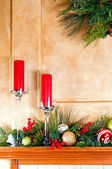 Candles and Christmas decorations on fireplace mantle — Stock Photo