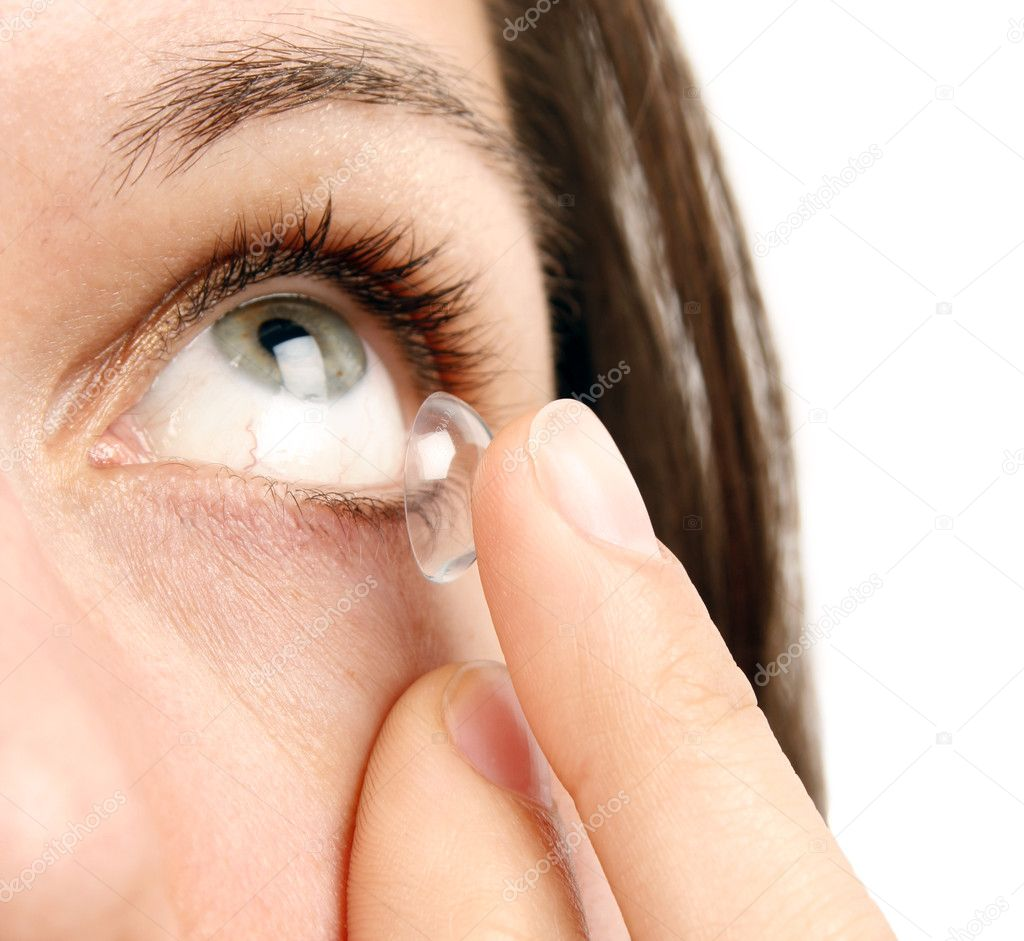 Woman inserting a contact lens  Stock Photo #4639621