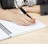 Businesswoman writing in her agenda — Stock Photo