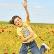 Happy boy jumping on field — Stok fotoğraf