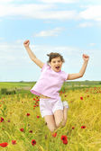 Happy girl jumping on field — Stock Photo
