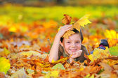 Boy in autumn forest playing with leaves — Stock Photo
