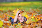 Kid playing with leaves — Stock Photo