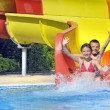 Children sliding down a water slide - Stockfoto