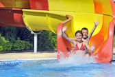 Children sliding down a water slide — Stockfoto
