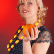 Woman with orange on a red — Stock Photo
