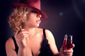 Woman in hat with wine red in glass with sigar — Stock Photo