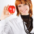 Young female doctor showing red apple — ストック写真