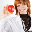 Young female doctor showing red apple - Stockfoto