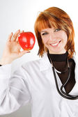 Young female doctor showing red apple — Stok fotoğraf