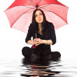 Woman sitting in water with umbrella — Stock Photo #4699488