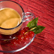 Espresso cofee with currants on black glass table — Stock Photo #4897785