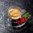 Espresso cofee with currants on black glass table — Stock Photo #4897826