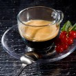 Espresso cofee with currants on black glass table — Stock Photo #4897854