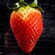 Red Strawberry on black glasstable — Stockfoto