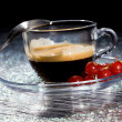 Espresso cofee with currants on black glass table — Stock Photo