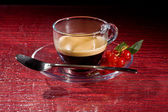 Espresso coffee with currants on red glasstable — Stock Photo