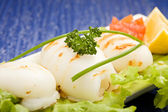 Squid with lettuce on blue glasstable — Stock Photo