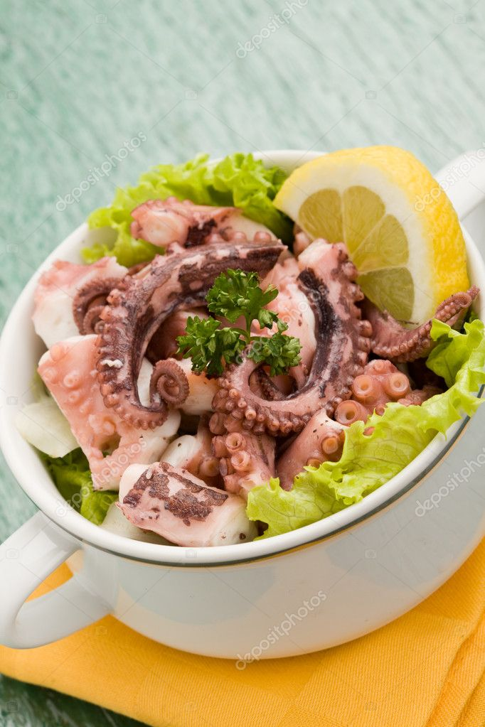 Photo of delicious octopus salad appetizer on green glass table with yellow cloth — Stock Photo #5128473
