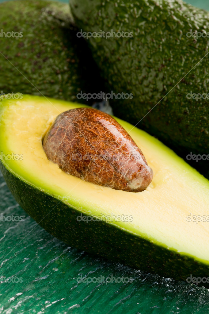 Photo of cutted avocado fruit on green glass table — Stock Photo #5221606
