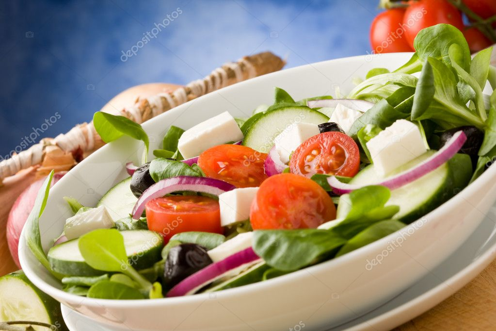 Photo of delicious greek salad on wooden table in front of blue background with spot light — Stock Photo #5338352
