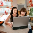 Two young women in the kitchen with a laptop - Stock Photo