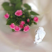 Angel and rose on ivory silk — Stock Photo