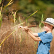 Stock Photo: Kid with straw hat playing with bulrush